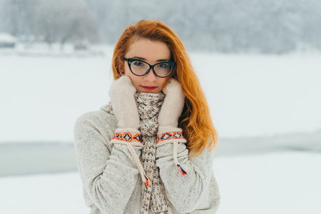 The beautiful young red girl in glasses is wrapped with scarf and wearing gloves in the forest covered with snow. Close-up portrait. Banque d'images