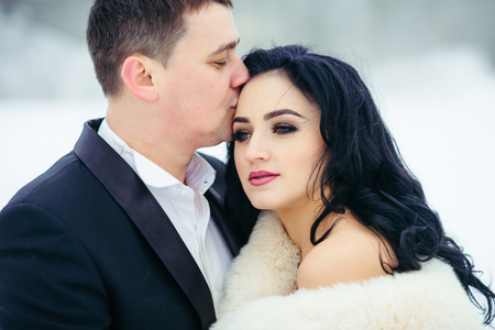 Horizontal portrait of the groom kissing the beautiful serious brunette bride into forehead. Winter time.