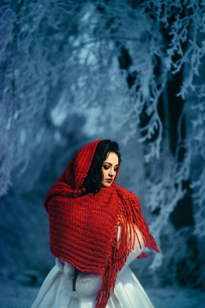 Vertical portrait of the charming brunette bride with red lipstick wrapped into red knitted scarf at night. Winter time.