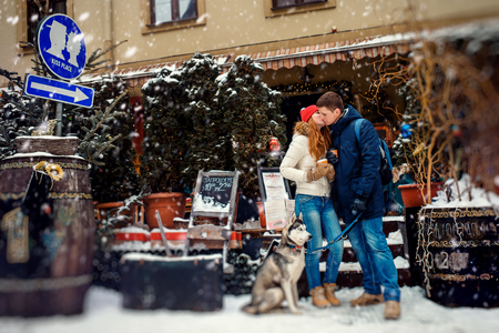 Walk of the happy couple with siberian husky. The beautiful red head woman is kissing the man in cheek near the sign Kiss Place during the snowfall.