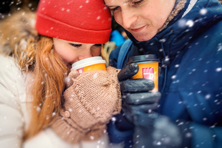 Close-up horizontal portrait of the attractive young couple drinking coffee and tea during the fluffy snowfall.