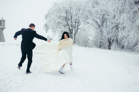 Happy newlywed couple is spending great time in the snowy forest. The groom is running after his beautiful brunette bride.