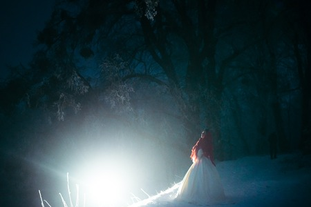 The full-length view of the beautiful bride covered in red knitted scarf and standing near the white light at the night snowy forest.