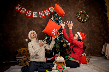 Indoor portrait of the cheerful couple of future parents throwing up pillows while sitting on the floor near the Christmas tree.