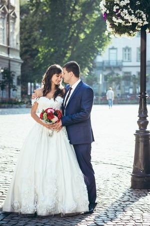 Happy attractive newlywed couple is softly hugging and touching noses in the sunny street. Full-length portrait.