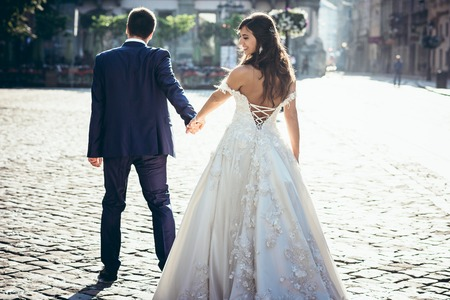 Back view of the groom leading the beautiful smiling brunette bride in the dress with the bare back along the sunny street.