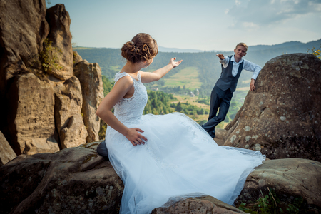 Newlywed couple is being apart and giving each other hand. The bride in the long dress is sitting on the stone while groom is leaning on the rock. Beautiful nature view.