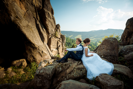 Young wedding couple is sitting back-to-back on the rock. Magnificent landscape view.