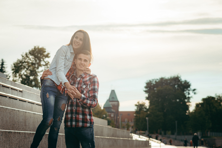 Happy couple in love. Emotional portrait. They are hugging in the sunny street. Stock Photo