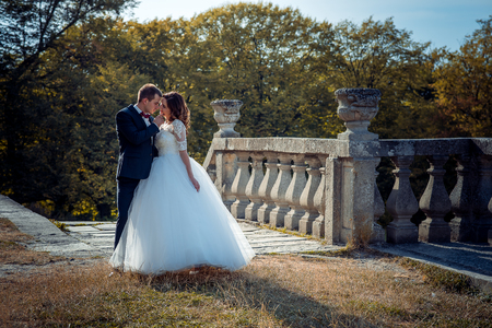 Full-length outdoor wedding shot of the beautiful cheerful newlywed couple. The groom is tenderly stroking the face of the charming smiling bride.