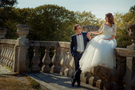 Full-length outdoor wedding portrait. The charming young bride is sitting on the old castle fence while groom is tenderly holding her hand.