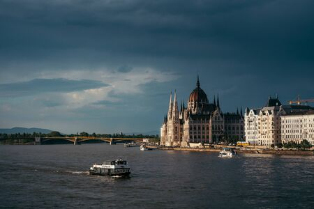 Panorama view of swimming boats along River Danube near the Budapest Parliament and Chain Bridge. Budapest, Hungary location.