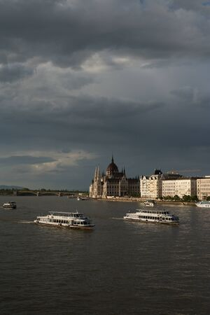 The grey clouds over River Danube full of driving boats. Landscape view of Budapest, Hungary. Standard-Bild - 143628075