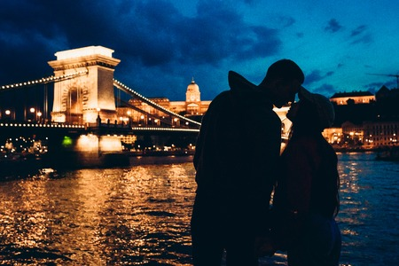 Romantic silhouettes portrait of the loving couple almost kissing at the background of the shining Chain Bridge on River Danube in Budapest, Hungary at night.