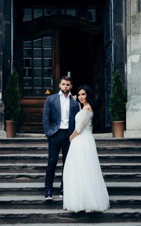 Full-length wedding shot of the beautiful young newlywed couple posing on the stairs of the old church.