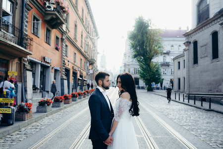 Wedding portrait of the attractive young couple tenderly holding hands in the town street. Stock Photo