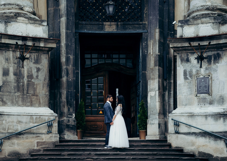 Charming young couple of newlyweds is softly holding hands and looking at each other while standing at the old stairs of the baroque church.