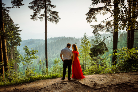 Romantic outdoor full-length portrait. Attractive couple is tenderly looking at each other with the smile while holding hands on the green rock during the sunset.