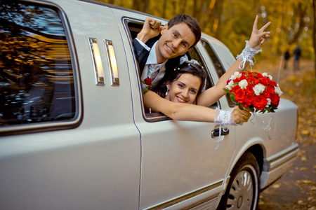 Happy charming newlywed couple is looking through the car window. The bride with the wedding bouquet of red roses is showing peace sign. Standard-Bild