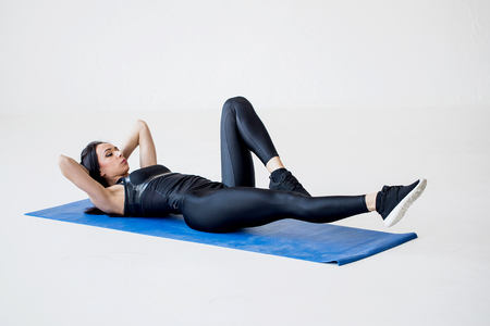 Close-up view of the sports charming woman lying on the mat and doing bicycle crunches in the white studio. Stock Photo