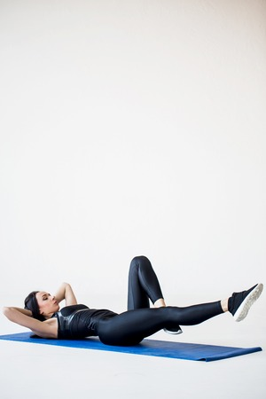 Sport tutorials for beginners. The young fitness girl is warming up by doing the bicycle crunches on the yoga mat in the white studio. Stock Photo