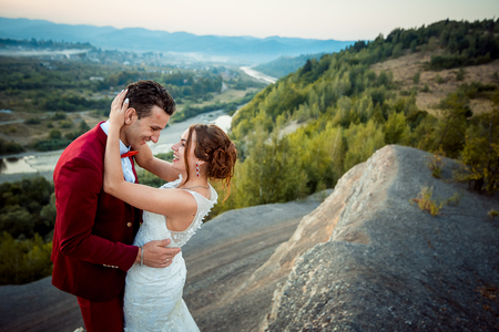 Adorable cheerful newlyweds are hugging at the background of the lovely landscape. The emotional wedding portrait. Stock Photo