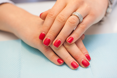 Female nails with red shellac on the table in beauty salon. Beauty and Treatment. Standard-Bild