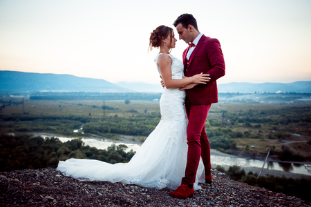 Cheerful newlywed couple is tenderly hugging on the mountains at the background of the landscape during the sunset.
