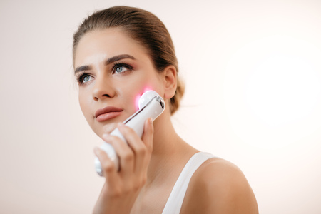 Young healthy woman with natural make-up using the facial massage machine