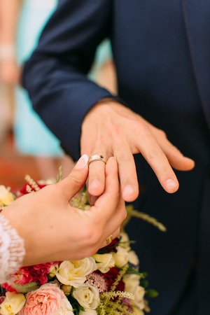 Bride is putting the wedding ring on the groom`s finger. Close-up view of hands.