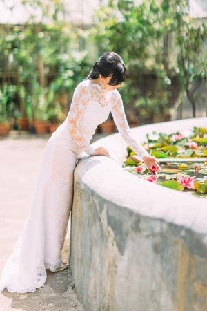 Beautiful bride touching the waterlilia in the fountain.