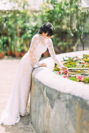 Beautiful bride touching the waterlilia in the fountain.