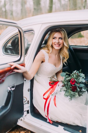 Beautiful blonde bride in white vintage car. Autumn forest on background
