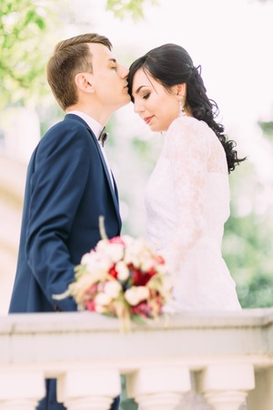 The groom is kissing the bride in the forehead. Half-length portrait.