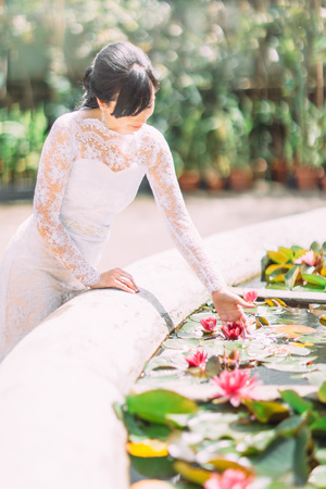 The side view of the bride touching the waterlilia in the fountain. Stockfoto