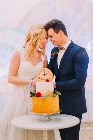 Beautiful blond bride and groom cut the wedding cake together