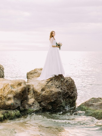 The side view of the bride with the sedding bouquet standing on the stone washed by the sea.