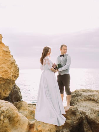 Back view of the newlyweds holding hands and looking down while standing on the cliff among the ocean.