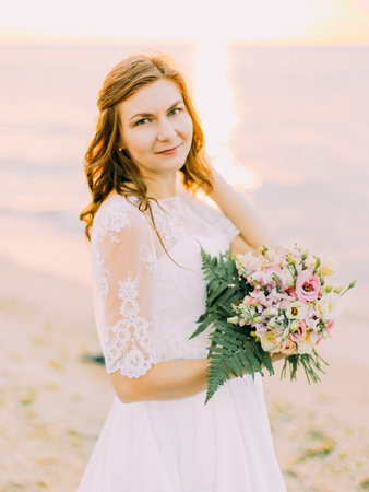 The close-up portrait of the bride holding the bouquet. The sunset composition. 写真素材