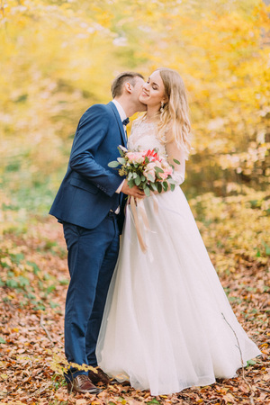 The groom is kissing the bride in the neck. Yellowed forest location.