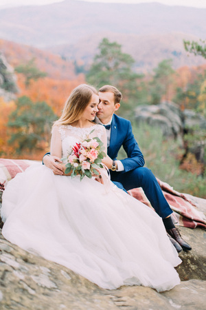 Romantic outdoor photo of the hugging newlywed couple sitting on the rocks. Reklamní fotografie