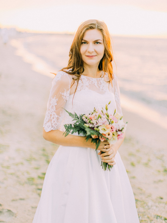 Smiling bride is holding the wedding bouquet of the roses at the background of the sea. The close-up portrait.