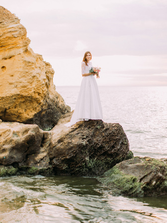 The full-length photo of the standing on the cliff bride at the background of the sea. 版權商用圖片
