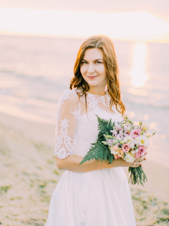 The lovely portrait of the smiling bride holding the wedding bouquet at the background of the sunset.