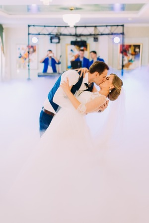 The full-length view of the kissing newlyweds during their fisrt dance on the smoked dancefloor.
