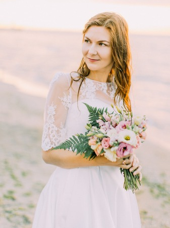 The portrait of the bride with the bouquet looking at the right side. The sunset composition.
