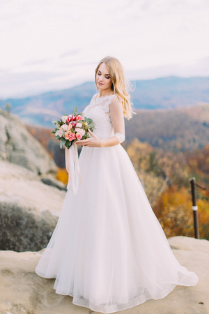 Full-length view of the bride holding and looking at the wedding bouquet while standing on the rock.