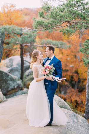 Romantic view of the hugging newlyweds standing on the rock at the background of the yellowed forest.