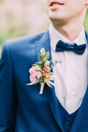 Der Boutonniere aus Rosen auf der Jacke des Bräutigams.
