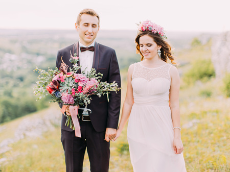 The smiling newlywed couple with closed eyes are holding hands. The groom is holding the wedding bouquet. The horizontal close-up view. Banque d'images